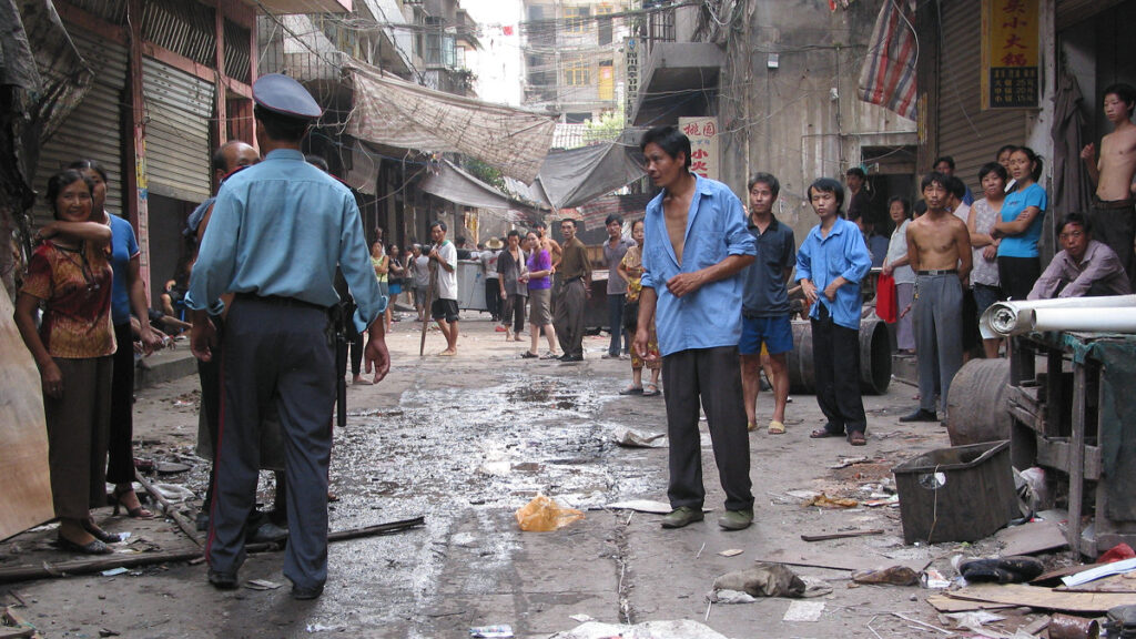 A photo of a street in an urban village, filled with men and women in work clothes